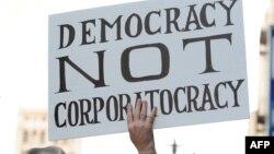 """Демонстрант со транспарент на кој пишува """"Демократија, а не корпорократија"""" на протести во Лос Анџелес на 3 октомври 2011 година."""