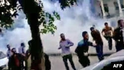 Antigovernment protesters run for cover from tear gas fired by security forces in the capital, Damascus, on April 29.