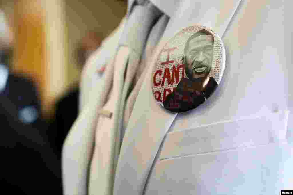 """I button that reads """"I can't breathe"""" adorns the jacket of a mourner before the funeral for George Floyd on Tuesday, June 9, 2020, at The Fountain of Praise church in Houston. Floyd died after being restrained by Minneapolis Police officers on May 25."""