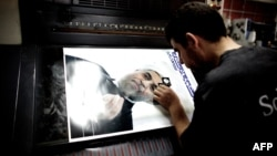 A man checks a printed electoral poster of presidential candidate and former top nuclear negotiator Hassan Rohani at a printing house in Tehran on May 26.