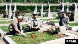 Қалмұқан Исабай (оң жақ), Әбдіғани Жиенбай (ортада) және Ержан Қарабек (сол жақта) Совет одағының батыры Мәжит Жүнісовтың қабірінің басында. Прага, Ольшанка зираты. Мамыр 2005 жыл