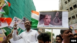 Activists in India hold photographs of Kulbhushan Jadhav, who has been condemned to death in Pakistan.