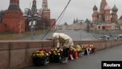 A woman adjusts flowers at the site of the assassination of Kremlin critic Boris Nemtsov in central Moscow in March.