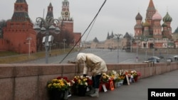 A woman adjusts flowers at the site of the assassination of Kremlin critic Boris Nemtsov in central Moscow, March 20, 2017