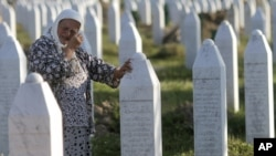 A woman cries next to the grave of her relative at the Potocari memorial cemetery near Srebrenica. (file photo)