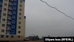 Построенный в микрорайоне Нурсат многоэтажный жилой дом по соседству с частными домами. Шымкент, 20 ноября 2015 года.