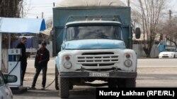 Жүк көлігіне газ отынын құйып тұрған адамдар. Алматы, 28 наурыз 2014 жыл.