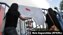 Protesters display a bed sheet with a red stain in the shape of Georgia at the protest outside the National Forensics Bureau.