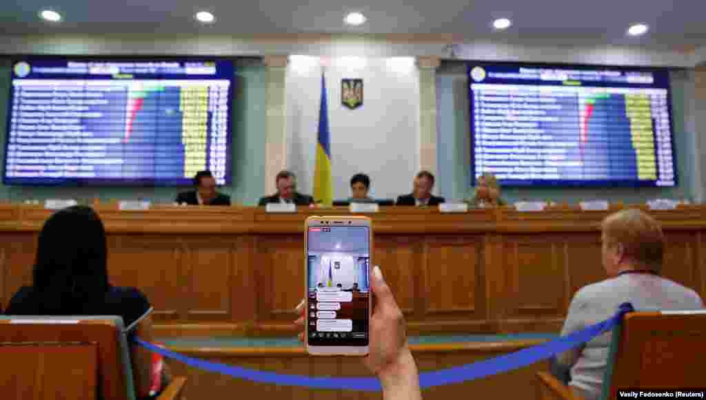 A journalist broadcasts a session of Ukraine's Central Electoral Commission live via a mobile phone in Kyiv, April 1, 2019. ( Reuters / Vasily Fedosenko)