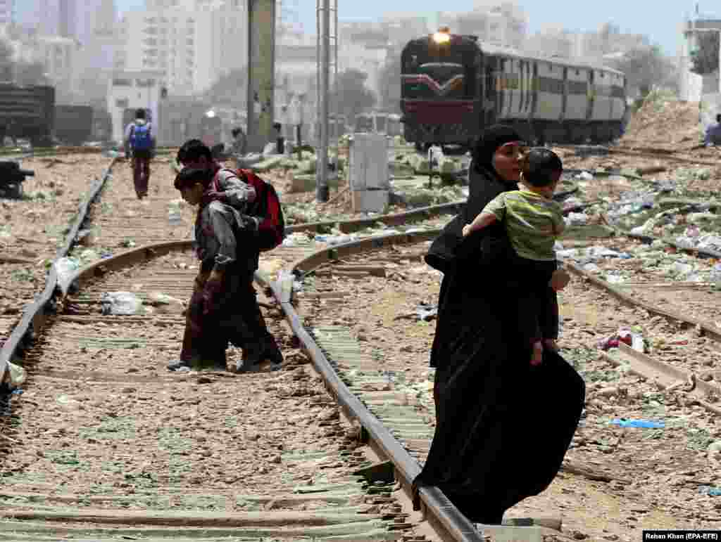 People cross rail tracks as a train arrives in Karachi, Pakistan. Every year, hundreds of people are killed or injured after being hit by trains in Pakistan. (EPA-EFE/Rehan Khan)