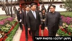 Сі Цзіньпін (л) і Кім Чен Ин на попередній зустрічі в Пекіні, 28 березня 2018 року