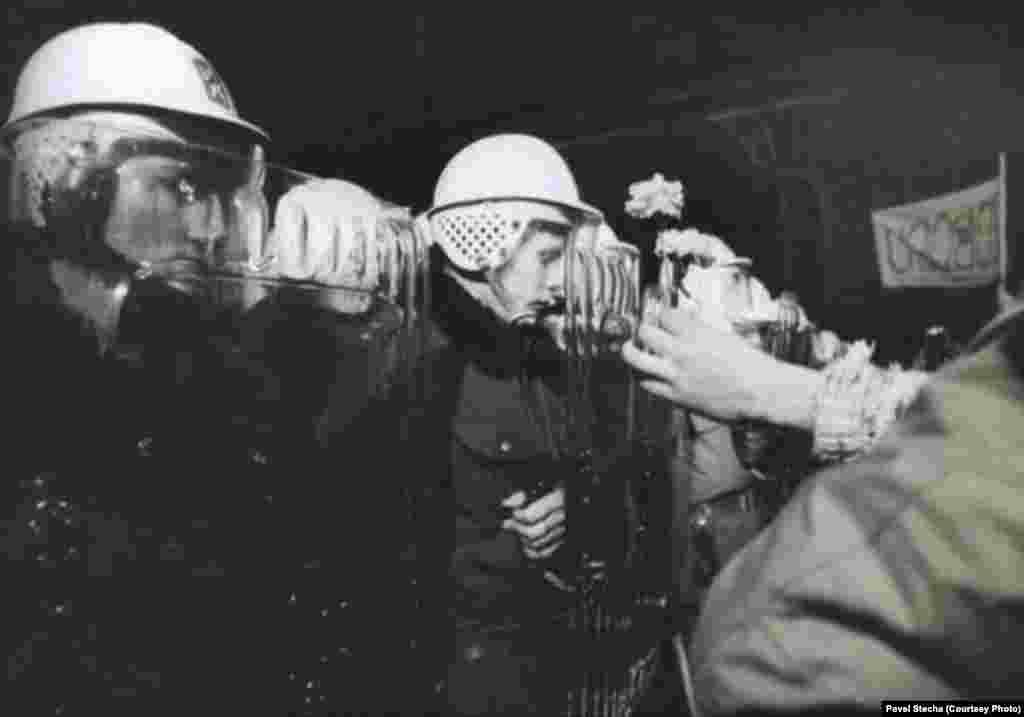 Тогда сотни человек пострадали во время противостояния. На этом фото женщина вручает цветы полицейскому, который остановил демонстрантов на Национальной улице.