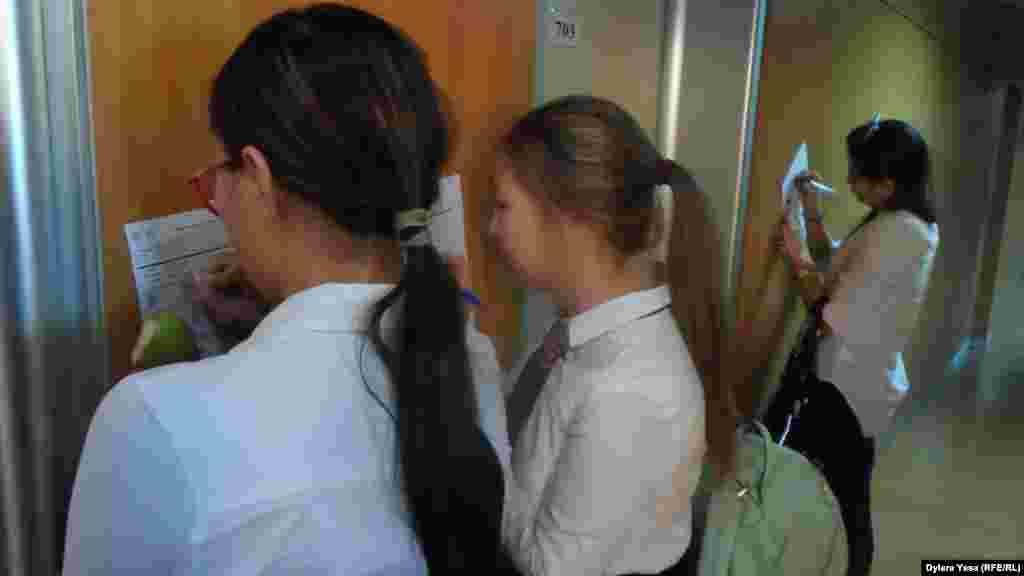 Девушки записывают нужные для себя сведения на выставке«Международное образование».