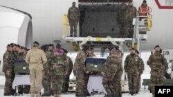 Sicriele soldaţilor francezi sunt încărcate în avionul care le va transporta în Franţa. Ceremonie oficială pe aeroportul din Kabul.