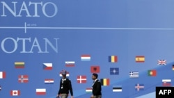 French soldiers walk past a wall decorated for the NATO summit in Strasbourg.