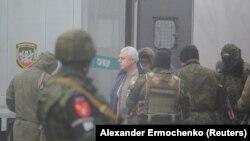 Бойовики російських гібридних сил супроводжують людей під час обміну утримуваними особами. Пункт пропуску Майорськ у Донецькій області, 29 грудня 2019 року