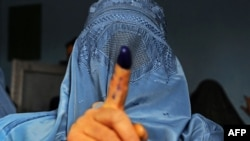 Afghanistan -- An Afghan woman shows her inked finger after voting at a polling station in the northwestern city of Herat, April 5, 2014