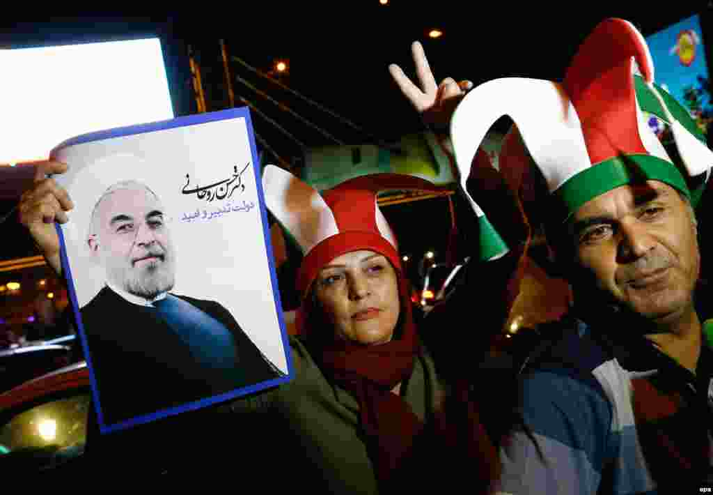 A couple holds a poster of Iranian President Hassan Rohani, who said that the nuclear deal would open a new chapter of international cooperation after years of sanctions.