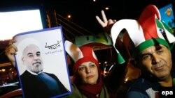 Иран президенти Хасан Роуханинин сүрөтүн көтөргөн адамдар. Тегеран, 14-июль, 2015-жыл