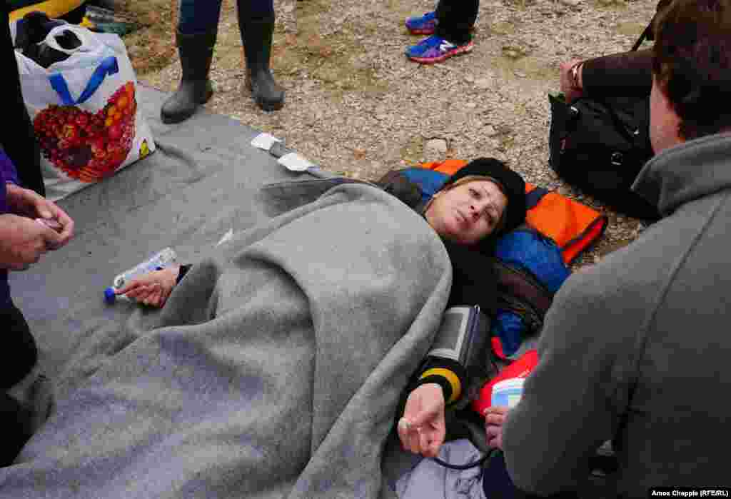 An unidentified migrant woman, who is pregnant, is treated by medical personnel after arriving on the Greek island Lesbos on February 26.