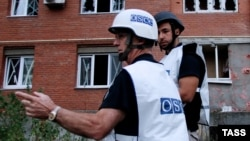 OSCE observers inspect a site near residential buildings damaged by recent shelling in Donetsk, eastern Ukraine.