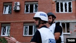 OSCE observers inspect a site near residential buildings damaged by recent shelling in Donetsk on September 9.