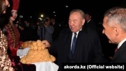 Kazakh President Nursultan Nazarbaev (center) is welcomed by Tatarstan's president, Rustam Minnikhanov, (right) in Kazan on June 14.
