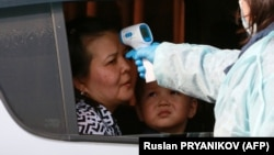 Дәрігер көлікте отырған тұрғынның дене қызуын тексеріп жатыр. Алматы, 19 наурыз 2020 жыл.