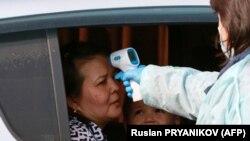 Медработник замеряет температуру пассажира автомобиля.