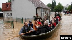 Serbian soldiers evacuate people in a boat in the flooded town of Obrenovac, southwest of Belgrade, on May 17.