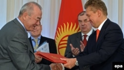 Kyrgyzgaz chairman Turgunbek Kulmurzaev (left) and Gazprom CEO Aleksei Miller (R) exchange documents during a signing ceremony in Bishkek sealing a deal for the Russian energy giant to buy the Kyrgyz corporation for a symbolic sum in April.