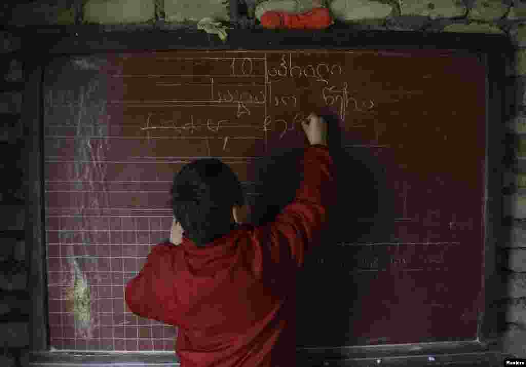 Bacho writes on his own personal blackboard.
