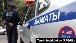 Сотрудник милиции у служебной машины.