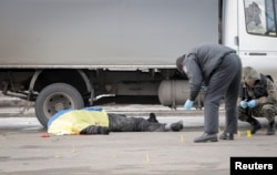 Police and forensic experts work next to the body of a victim covered by a Ukrainian national flag at the site of an attack on a Peace March in Kharkiv on February 22 that killed four peoople.