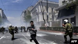 A demonstrator runs away from riot police during a protest in Athens on May 11, 2011
