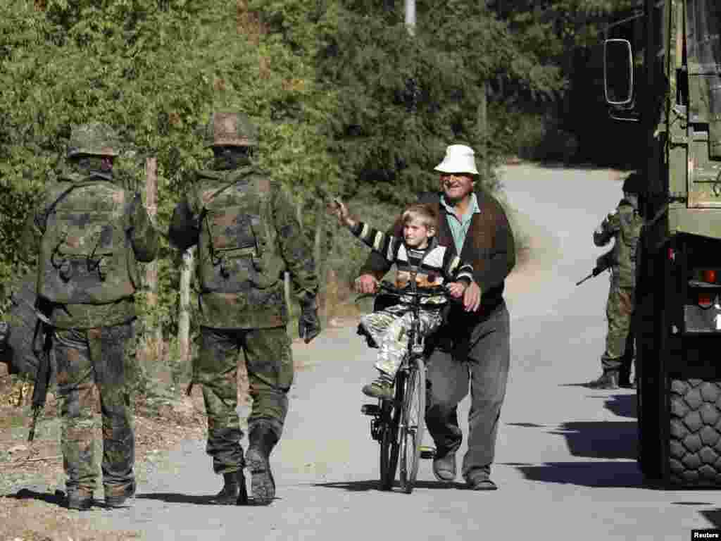 An ethnic Albanian pushes a boy on a bicycle pass KFOR German soldiers, part of the NATO mission in Kosovo, in the village of Cabra. (Hazir Reka for Reuters)