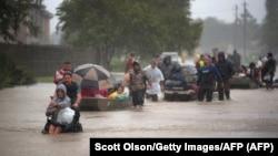 Люди пытаются спастись от наводнения в Хьюстоне. 28 августа 2017 года.