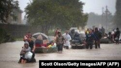 Люди прямують затопленими вулицями передмістя Г'юстона, рятуючись від наслідків урагану «Гарві», 28 серпня 2017 року