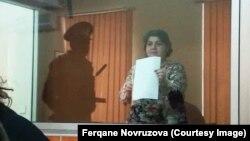 Сот залындағы дыбыс өткізбейтін орыннан түрмедегі құқық бұзушылық туралы ақпарат таратып тұрған әзербайжандық журналист Хадиджа Исмаилова. 2016 жылдың қазаны.