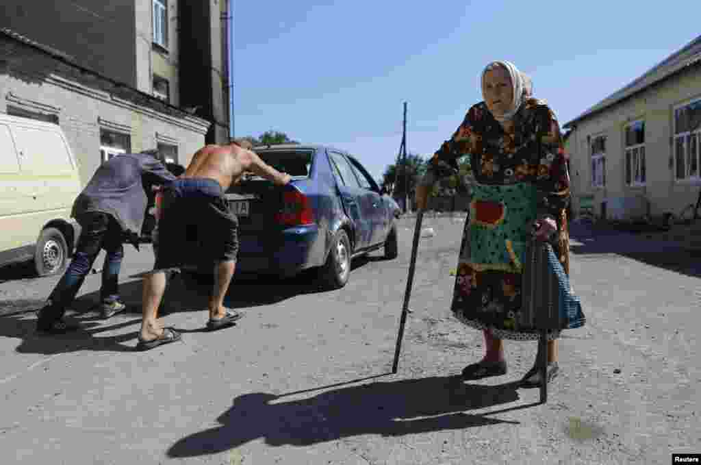 People push a broken-down car past a woman in the eastern Ukrainian town of Ilovaysk. (Reuters/Maxim Shemetov)