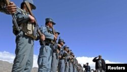 Uniformed police of the Daychopan district welcome local government officials to a meeting in the district in Zabul Province in 2011.