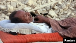 A survivor of the Balochistan earthquake sleeps near the rubble of his mud house.