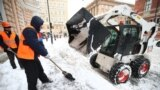 Utility workers shovel snow on Suvorovsky Prospekt Street in St. Petersburg on January 10.