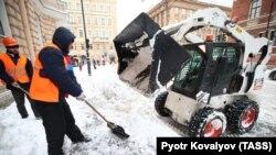 Utility workers shovel snow on Suvorovsky Prospekt Street in St. Petersburg on January 10.