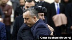 Afghan President Ashraf Ghani hugs his first vice president candidate Amrullah Saleh, after arriving to register as a candidate for the upcoming presidential election at Afghanistan's Independent Election Commission (IEC) in Kabul on January 20.