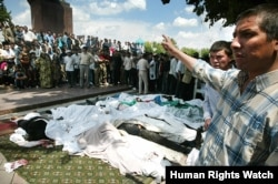 A man gestures to the bodies of victims killed in Andijon on May 14, 2005, the day after the violence.
