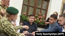 Прикордонник (ліворуч) подає протокол про адміністративне правопорушення колишньому грузинському президенту Міхеїлу Саакашвілі (в центрі) біля готелю у Львові, 12 вересня 2017 року