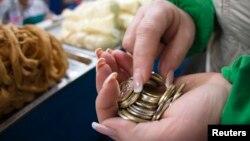 Монеты в руках продавца на рынке в Алматы.