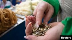 Женщина считает деньги на базаре в Алматы. Иллюстративное фото.