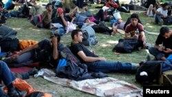 Migranți din Orientul Mijlociu și Asia se odihnesc într-un parc înainte de a-și continua drumul spre Ungaria, Belgrad, 22 iulie 2016
